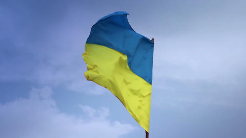 Ukrainian national flag waving on flagpole in blue sky. Ukraine Footage