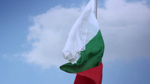 Bulgarian national flag waving on flagpole in blue sky. Bulgaria Footage