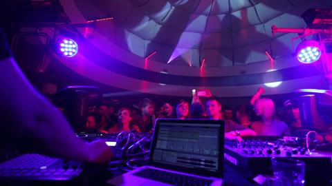 Clubbing people on dance floor as DJ performs music set Footage
