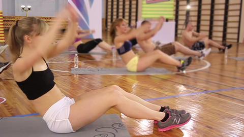 Young female works out in gym. Exercise for abs performed by group of sportsmen Footage