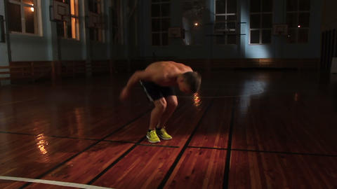 Young muscular athlete works out with jumps and push-ups in gym in slow motion Footage