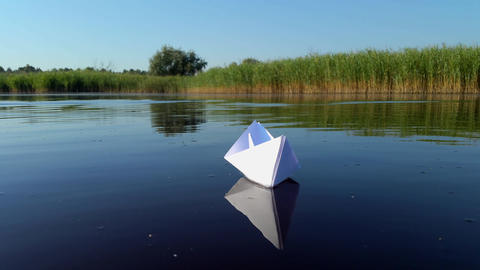 Ship of white paper floating in the river Footage