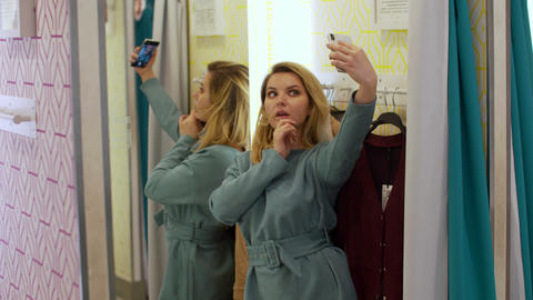 Nice girl makes a selfie on her phone in the fitting room Footage