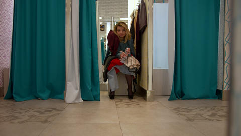 Young woman sits in the fitting room and is waits for something Footage