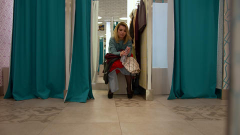 Girl sits in the fitting room with a bunch of clothes Footage