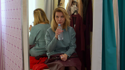 Tired girl is sitting in the fitting room and drinking water Footage
