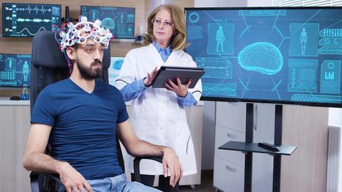 Female neurologist reading data from brainwave scanning headset Archivo