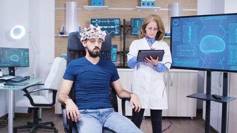 Female doctor checking the brain activity of male patient ビデオ
