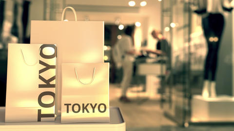 Paper shopping bags with TOKYO text against blurred store. Japanese shopping GIF
