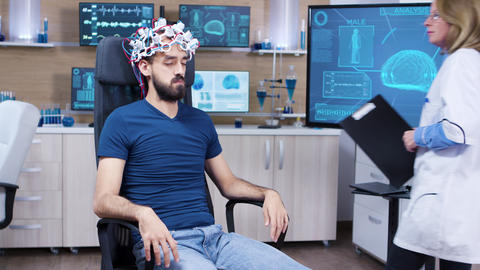 Patient with brainwaves scanning headset closing his eyes ビデオ