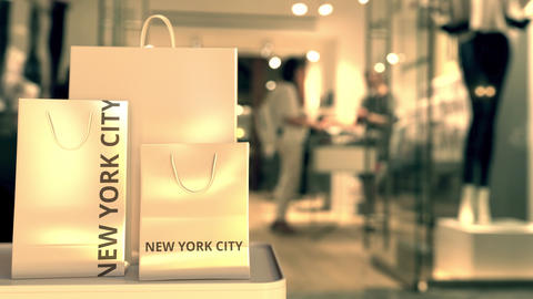 Shopping bags with NEW YORK CITY text against blurred store. American retail GIF