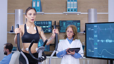 Female scientist monitoring the heart activity on female athlete Live Action