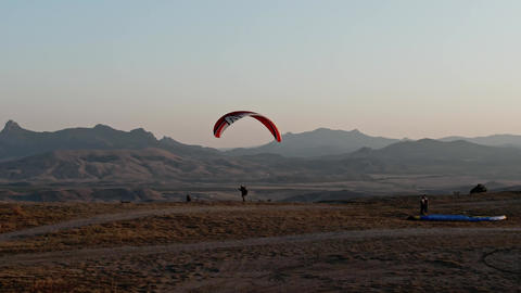 Man with the parachute catching the wind while standing on the rock face Footage