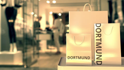 Shopping bags with DORTMUND text against blurred store. German shopping related GIF
