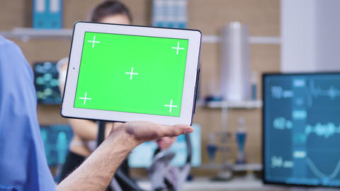 Dolly shot of doctor in sport science holding tablet with green screen Live Action