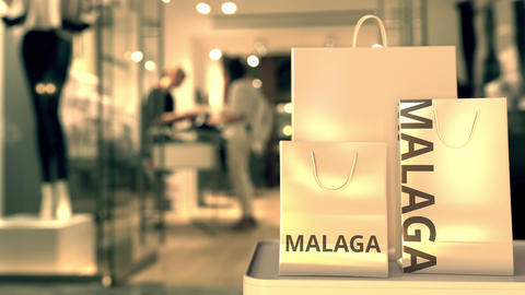 Paper shopping bags with MALAGA text against blurred store. Spanish shopping GIF