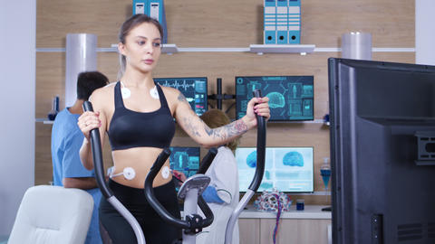 Female athlete running with electrodes attached to her body Footage