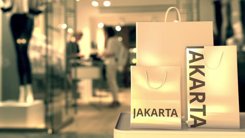 Paper shopping bags with JAKARTA text against blurred store. Indonesian shopping GIF