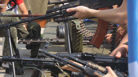 People are looking at and holding Russian machine guns and guns in their hands Archivo