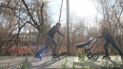 Sporty cheerful parents enjoy a walk in a warm park on roller skates with a baby GIF