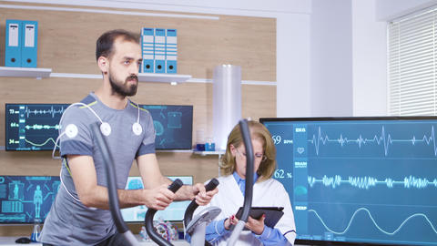 Female doctor in sport science checking male athlete performance Live Action
