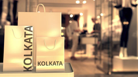 Shopping bags with KOLKATA text against blurred store. Indian retail related Footage