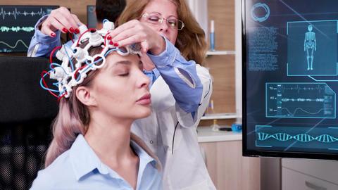 Female doctor in brain science lookin at tv screen Archivo