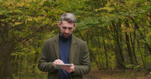 Handsome Caucasian tourist standing in the autumn forest, typing on his tablet Footage