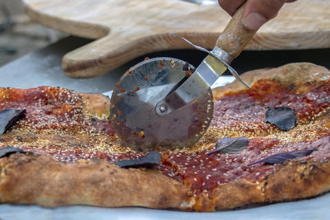 Pizza with tomato sauce, sesame and basil. With reflection in the cutting tool Photo