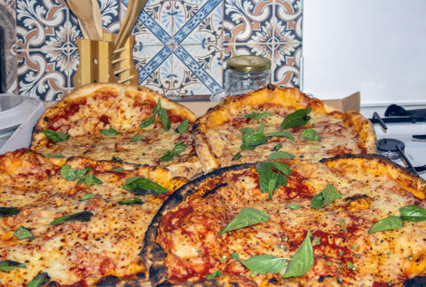 Pizza with tomato sauce, cheese and basil in the kitchen Photo