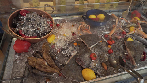 Mixed seafood: mussels, gobies, flounder, king prawns on an ice counter in a ビデオ