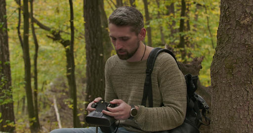 Handsome adult Caucasian tourist sitting in the autumn forest and checking his Footage