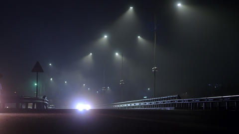Cars drive at night on a wet foggy road. Dangerous night driving. Lights on the Live Action