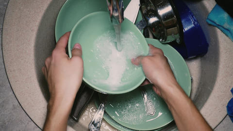 Woman washing dishes with a sponge GIF