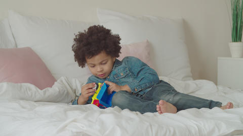 Serious cute little kid repairing toy car on bed Footage