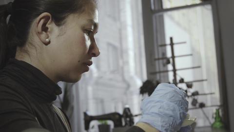 Asian woman glazes pottery in workshop GIF