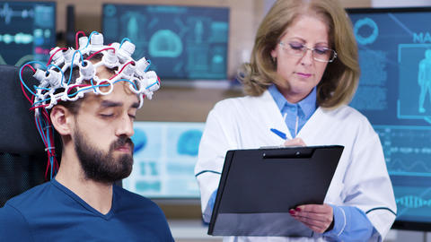 Female doctor taking notes while patient is wearing brains sensors ビデオ
