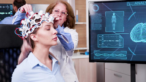 Female scientist checking the brain activity of her patient ビデオ
