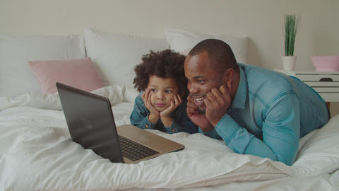 Black father and son streaming cartoons online GIF
