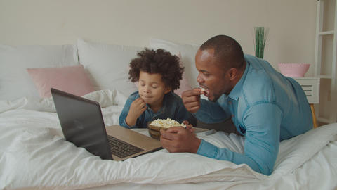 Family with popcorn streaming movie online on bed GIF