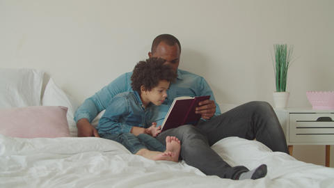 Joyful diverse family reading a book lying on bed Archivo