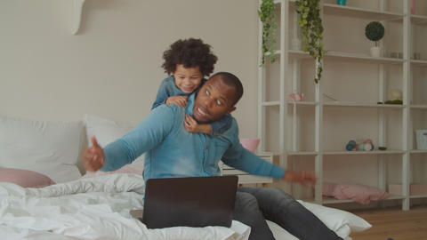Playful son embracing busy black dad in bedroom Live Action