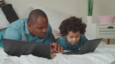 Caring black dad teaching son using laptop at home GIF