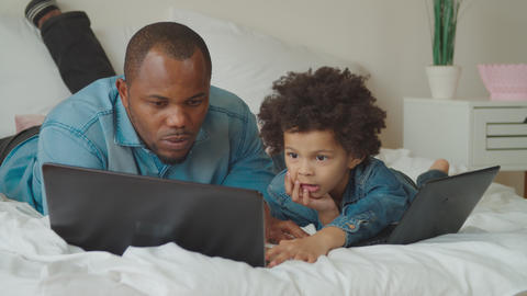 Positive father and son working on laptop on bed GIF