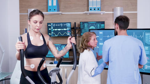 Female doctor in sport science checking the energy of female athlete on tv Live Action