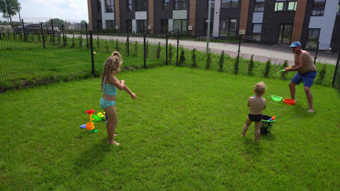 Playful dad shooting at his daughter with water gun. Father catching little girl GIF