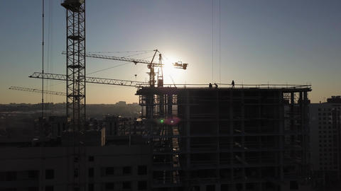 Construction Site at sunset. Silhouette of a construction crane near the Live Action