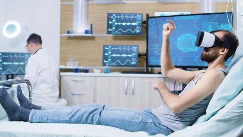 Patient sitting on hospital bed wearing virtual reality goggles GIF