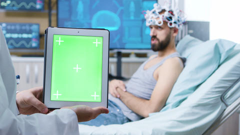 Doctor in a neurology clinic holding tablet with green screen GIF