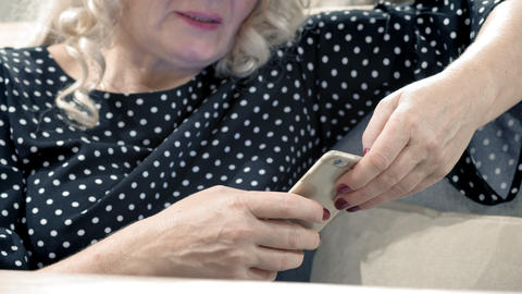 Old woman using new smartphone. Prints a text message on a smartphone. Modern Live Action